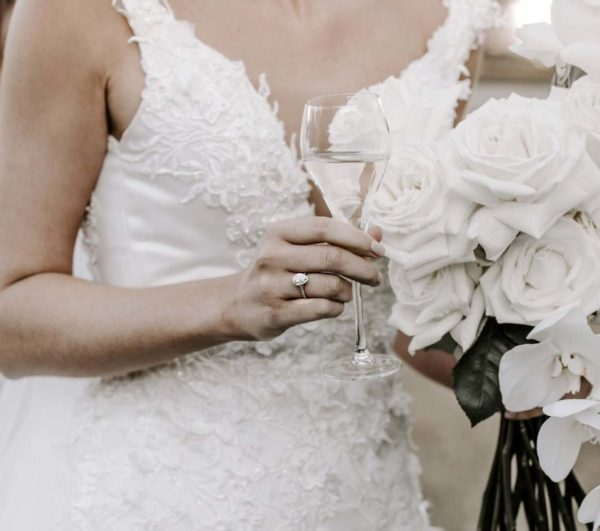 bride holding wine and wedding ring